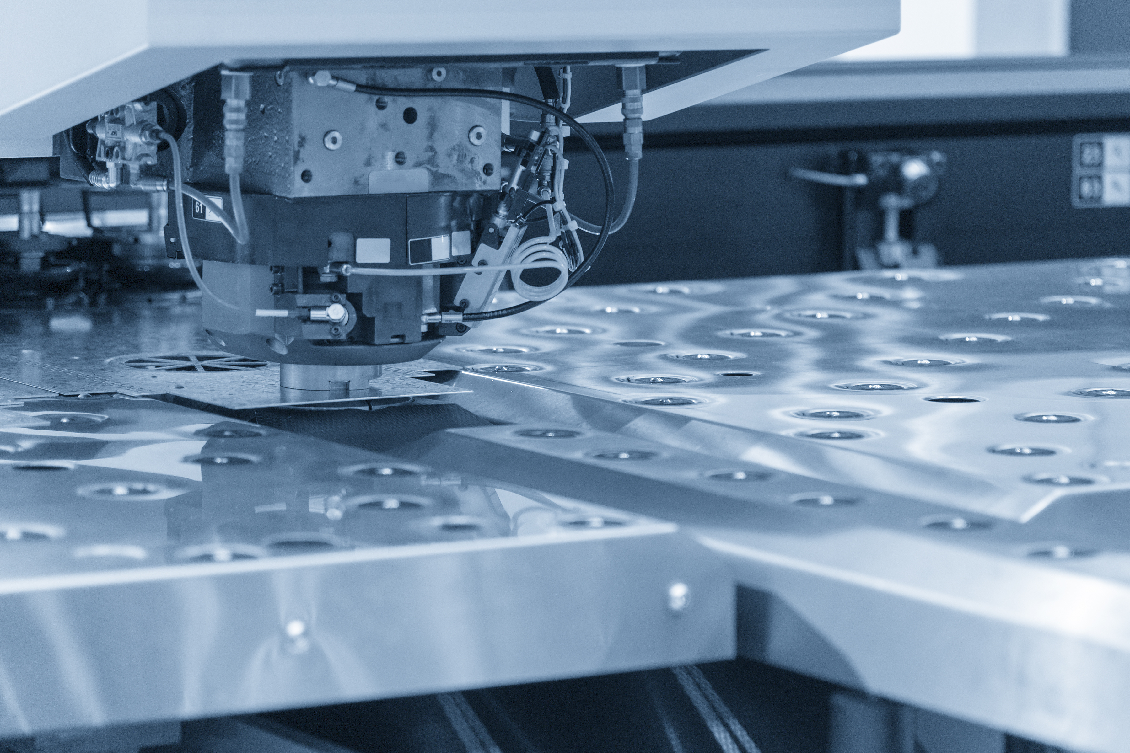 The hi-speed turret punching machine for sheet metal piercing process control by CNC program. The modern sheet metal production by turret punching machine.